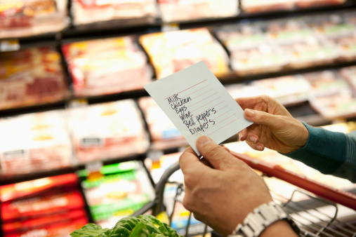 Older woman reading grocery list in supermarket